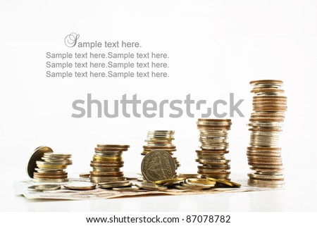 Stack of coins with bank notes isolated on white background