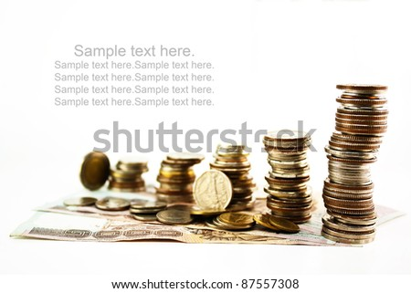 Stack of coins with bank notes isolated on white background.