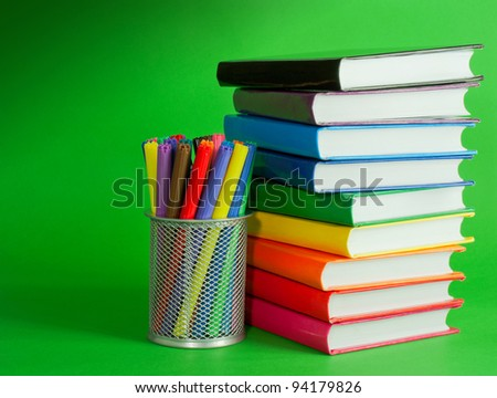 Stack of colorful books and socket with felt pens against green background