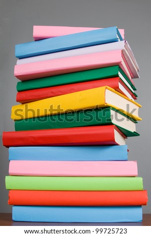 Stack of colorful books on a gray background - stock photo