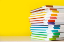 Stack of colorful books on color background.
