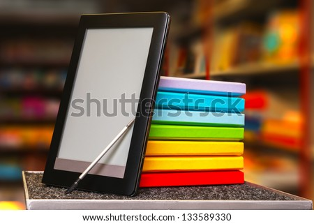 Stack of colorful books with electronic book reader at a book store