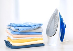 Stack of colorful cotton clothes and iron.Household laundry ironing.
