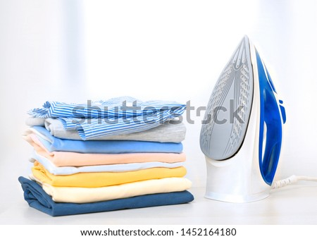 Photo of  Stack of colorful cotton clothes and iron.Household laundry ironing.