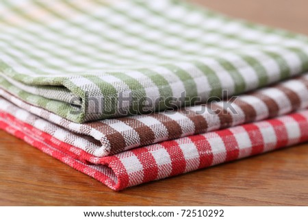 Stack of colorful dish towels on wooden table. Shallow dof