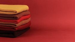 Stack of colorful folded sweaters on brown maroon background with copy space