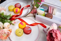 stack of colorful modern cakes cookies macaroons on plate  for celebration romantic party birthday pion flowers, satin ribbon top view, many different types flavors of macarons dessert drawn decorated