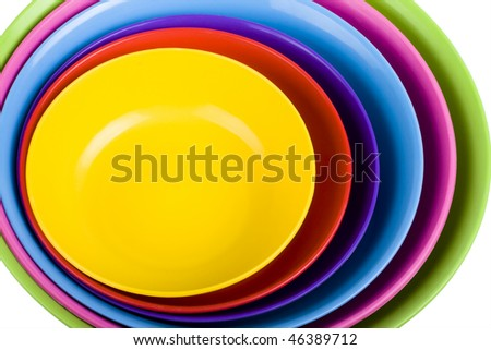 Stack of colorful plastic bowls over white background