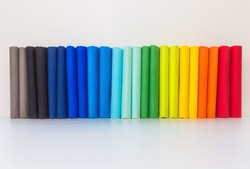 Stack of colorful spectrum t-shirts, folded 2 for each color t-shirts on white background.