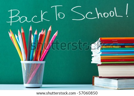 Stack of colorful textbooks and copybooks with pencils near by on background of blackboard