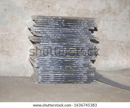 stack of compact discs on plywood and concrete wall