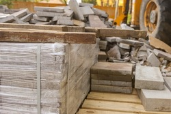 Stack of concrete paving stones. Repair pavement and laying paving slabs. Building materials for road construction of city, sand filling. Road tiles and curbs