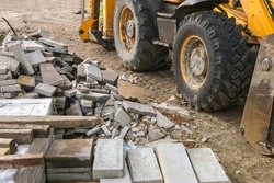 Stack of concrete paving stones with tractor background. Repair pavement and laying paving slabs on walkway. Building materials for road construction of city, sand filling. Road tiles and curbs