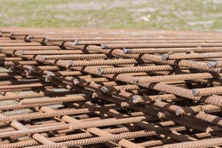 Stack of constructions welded from reinforcing steel slightly covered with rust intended for the manufacture of reinforced concrete, close-up in selective focus