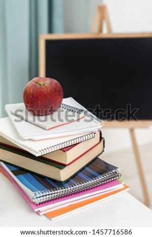Stack of copybooks and textbooks at desk