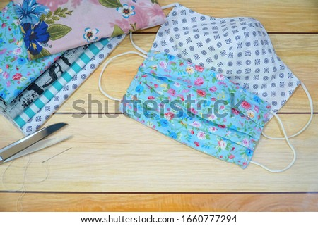 Stack of cotton, scissor, needle and DIY  fabric mask on wood table. Protect dust, pollution (PM2.5), Virus, Bacteria. Handicraft, Handmade concept. Copy space for any text design.