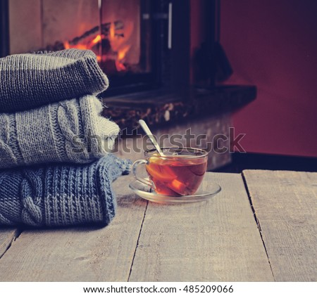 Stack of cozy knitted sweaters and cup of hot tea with lemon on old wooden table, near burning fireplace and cat sitting at background