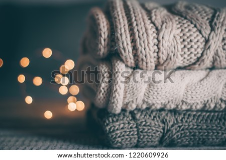 Stack of cozy knitted sweaters and garland lights on wooden background. Autumn-winter concept. Magic, cozy and mood time #1220609926