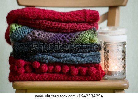 Stack of cozy knitted sweaters and other cloth, candles on the wooden chair, seasonal concept of warming, copy space, autumn fall winter background #1542534254
