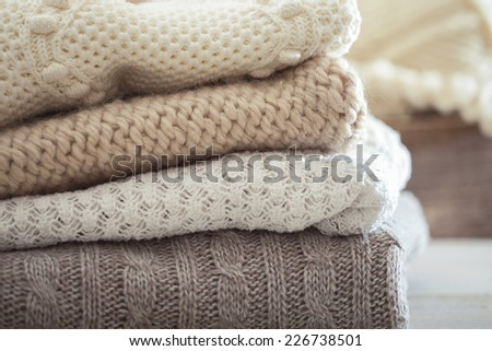 Stack of cozy knitted sweaters on a wooden table. Retro style. Warm concept