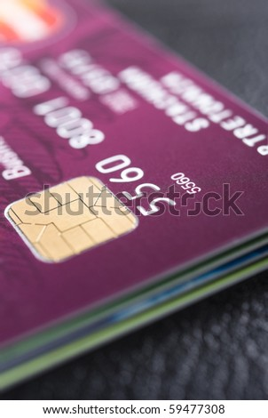 Stack of credit cards with details of a card with its chip and some numbers
