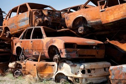 Stack of damaged rusted car scraps on junkyard