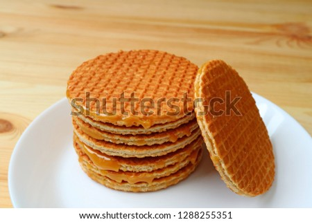 Stack of delectable Stroopwafel or caramel filled Dutch waffle served on white plate on wooden table