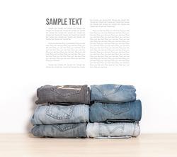 stack of denim jeans isolate on wooden desk