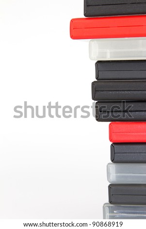 Stack of different colored DVD cases in front of a white background