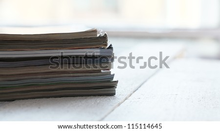 Stack of different magazines on the wooden table