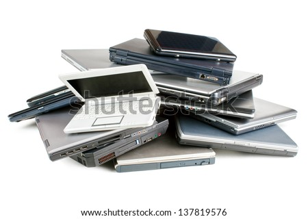 Stack of different sized and aged laptops, isolated on white background with shadow