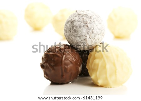 stack of different truffle pralines in front of yellow truffles on white background