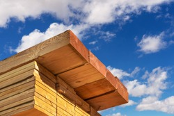 Stack of dimensional lumber for home construction with partly cloudy sky.