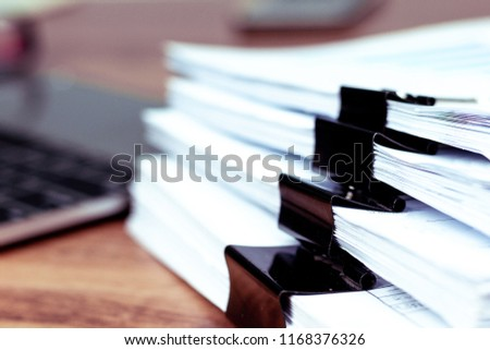 Stack of documents placed on a business desk in a business office. #1168376326