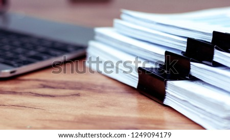 Stack of documents placed on a business desk in a business office. #1249094179