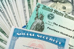 Stack of 100 dollar bills with US Treasury illustrative check to illustrate American Rescue Plan Act of 2021 payment with social security card for retirees