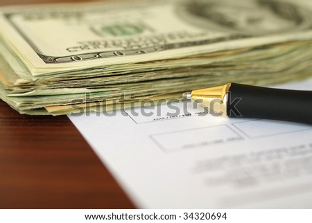 Stack of dollars and pen on a document page - stock photo
