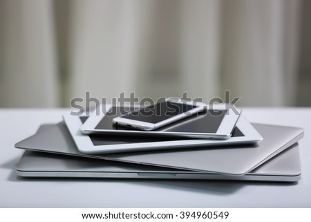 Stack of electronic devices on a white desk