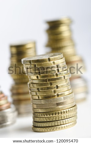 Stack of euro coins with money in background