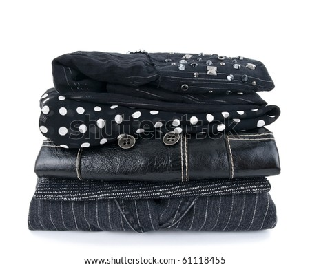 Stack of fashionable black clothes on white background.
