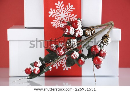 Stack of festive red and white theme Christmas gift boxes on reflective white table against a red background. Closeup on holly decoration.