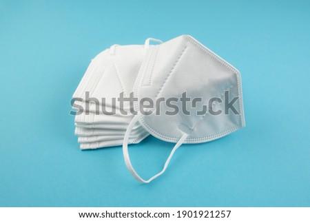 stack of FFP2 or N95 respirator face masks on blue background