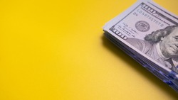 Stack of fiat money with face value of one hundred US dollars on yellow surface. Space for text. Concept of profit and successful investment. Close-up