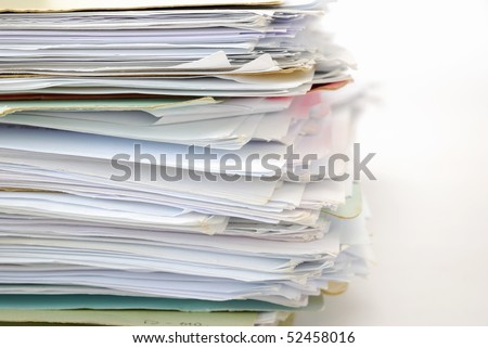 Stack of files full of documents signifying concepts such as work and stress, and business objects.