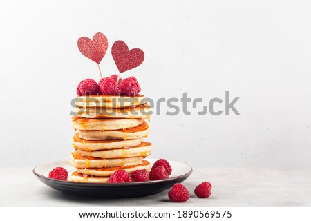 Stack of fluffy pancakes with syrop, decorated with red hearts and raspberries. Homemade present for Saint Valentine day. Light background. Copy space.