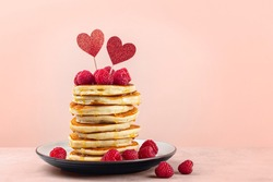 Stack of fluffy pancakes with syrup, decorated with red glitter pepper hearts and raspberries. Homemade present for Saint Valentine day. Light peach colour background. Copy space.