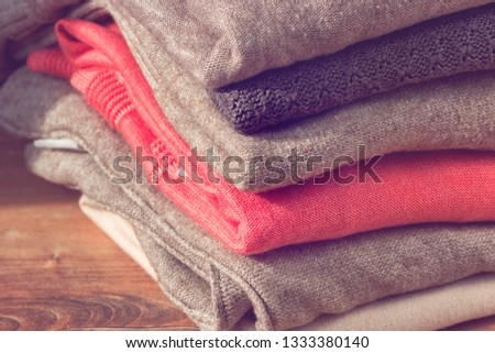 Stack of folded beige and pink clothes on brown wooden background. Female blouses pile.