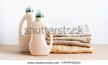 Stack of folded clean clothes things with Eco Design mockup blank bottles packaging of detergent for laundry on white background. Space for text. Bio organic product. #1499946263