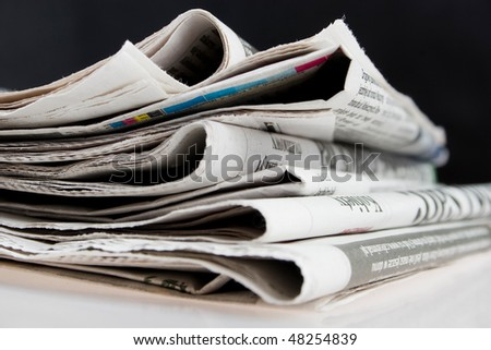 Stack of folded newspapers on black background