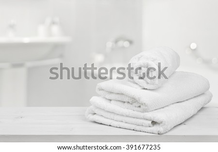Stack of folded white towels over blurred bathroom background